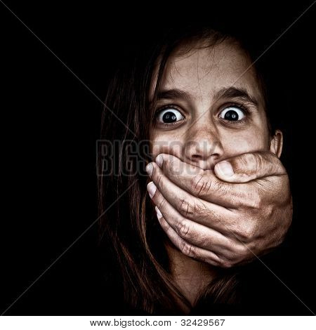 Portrait of a scared girl being abused by an adult man who covers her mouth with his hand (only his hand is visible, the rest is hidden in the shadows)
