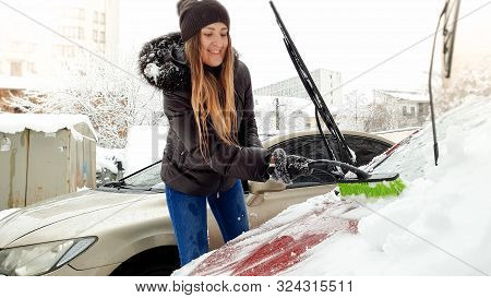 Close Up Shot Of Young Smiling Blond Woman In Brown Jacket Hat Gloves And Blue Jeans Trying To Clean