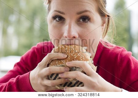 Close Up Portrait Of Hungry Girl Is Eating Fast Street Junk Food. Young Woman Biting Tasty Yummy Bur
