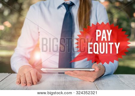 Word writing text Pay Equity. Business concept for eliminating sex and race discrimination in wage systems Female business person sitting by table and holding mobile phone. poster