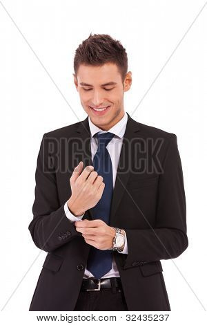 young smiling business man buttoning his sleeve and getting ready to work