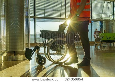Modern Airport Terminal With Staff Walking With Wheelchair And Sunflare In The Background Sunset Ref