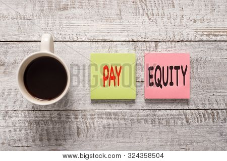 Handwriting text writing Pay Equity. Concept meaning eliminating sex and race discrimination in wage systems Stationary placed next to a cup of black coffee above the wooden table. poster