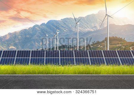 Asphalt Road With Solar Panels With Wind Turbines Against Mountanis Landscape Against Sunset Sky,alt