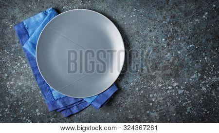 Empty Ceramic Gray Round Plate With Blue Linen Napkin