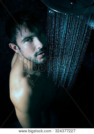 Sexy Portrait Of Handsome Naked Man With Beard And Blue Eyes Under A Rainfall Shower Looking Directl