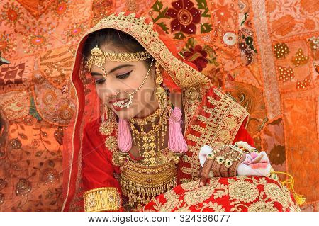 Jaisalmer, India - February 17, 2019: Indian Girl Dressed In Red Sari And Adorned With Traditional I