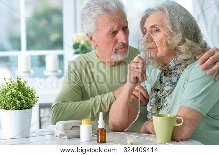 Close-up Portrait Of An Elder Couple Making Inhalation