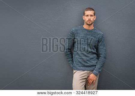Handsome young cool man standing on grey background and looking at camera. Portrait of thoughtful casual man. Pensive stylish guy wearing sweater leaning against background with copy space.