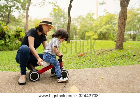 Young Asian Mother Teaching Her Adorable Toddler Girl To Ride The Bike For The First Time While Spen