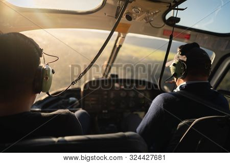 Scene Of Soft Blurry Helicopter Cockpit From The Rear Side Which Have Two Pilots At The Front Seat W