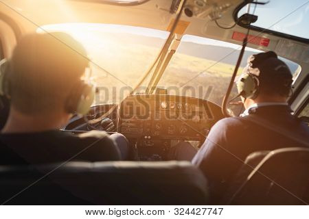 Scene Of Helicopter Cockpit From The Rear Side Which Have Two Pilots At The Front Seat, While Flying