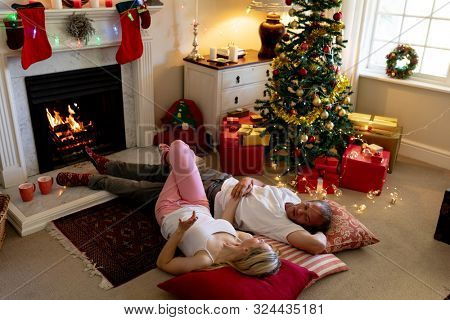 High angle view of a Caucasian couple lying on the floor by the fireplace in their sitting room at Christmas time, looking at each other, holding hands and smiling, with a decorated Christmas tree in