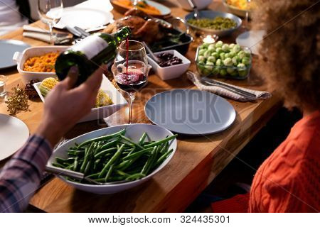 Over the shoulder view of a young mixed race man sitting at a table at home set for Thanksgiving dinner pouring a glass of red wine from a bottle for a young mixed race woman sitting at the table