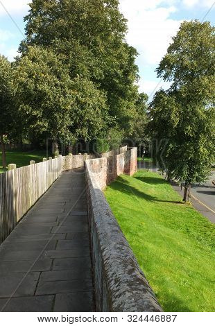 A View Along The City Walls In Cheshire Surrounded By Trees And A Grass Embankment