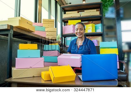 Online Shopping Young Start Small Business In A Cardboard Box At Work.the Seller Prepares The Delive