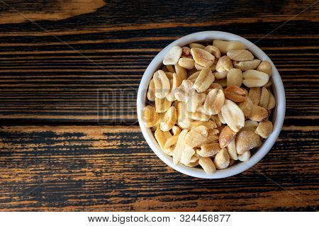Salted Peanuts In Bowl On Wooden Background. Delicious Peanuts Containing Vitamins And Amino Acids: