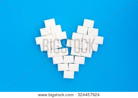 Broken Heart From Sugar Cubes, Blue Background. The Concept Of Problems Associated With High Blood S