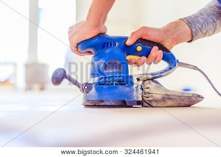 Close up of a sander power tool for DIY on wooden parquet floor poster