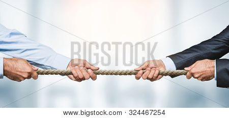 Tug Of War, Two Businessman Pulling A Rope In Opposite Directions Over Defocused Background With Cop
