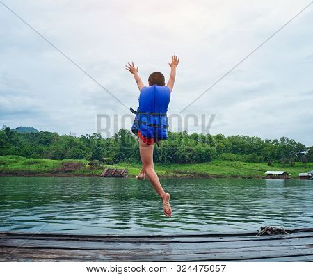 Safety Of Life Concept. Little Caucasian Boy Uses A Life Jacket, Jumping Off A Wooden Dock Into The