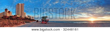 Miami South Beach sunrise with hotels and coastline with colorful cloud and blue sky.