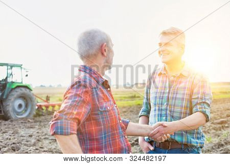 Mature farmer shaking hands with senior farmer in field with yellow lens flare in background