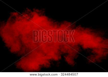 Red Powder Explosion Cloud On Black Background. Freeze Motion Of Red Color Dust  Particles Splashing