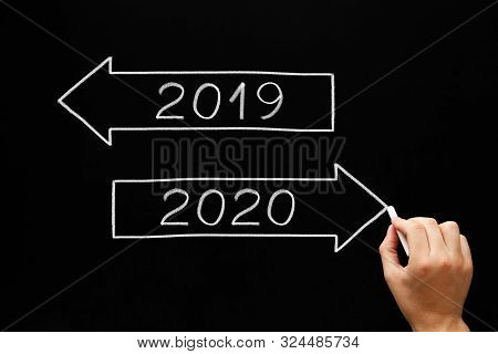 Hand Drawing New Year Beginning Arrows Concept With Chalk On Blackboard. Going Ahead To Year 2020 An