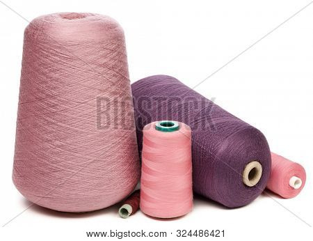 Group of cones and spools of pink and violet synthetic or cotton threads isolated on white background used for weaving in textile manufacturing