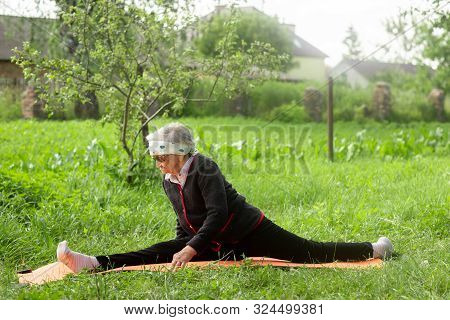 An Elderly Woman Of 90 Years Old, With Gray Hair And A Headband, Makes A Longitudinal Split In The S