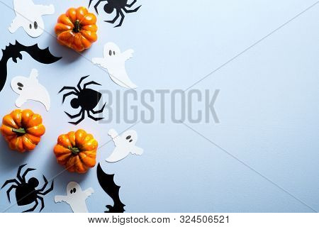 Happy Halloween Holiday Concept. Halloween Decorations, Spiders, Bats, Ghosts, Pumpkins On Blue Back
