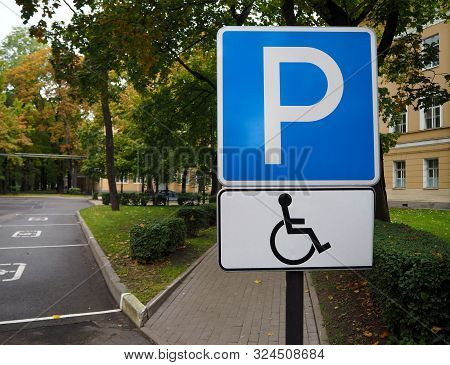 Blue Road Sign For Disabled Parking With Autumn Trees On Background. Empty Disabled Parking Spaces.
