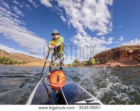 senior man paddling a stand up paddleboard against head wind on mountain lake - Horsetooth Reservoir , Colorado, in early fall scenery