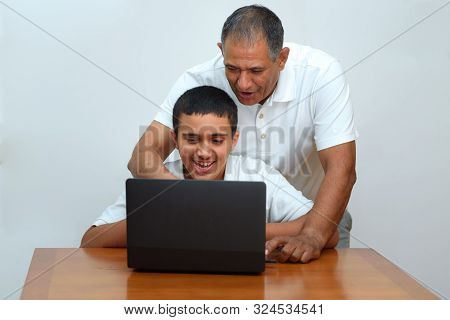 Senior Father And Teenage Son Using Laptop. Boy And Dad Sitting At Home Working With Tablet Computer