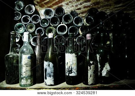 Very Ancient Bottles Of Wine Lies In Retro Dark Cellar. Rare Vintage Bottles Of Wine In Unique Cella