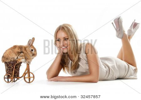 Photo of cute brown rabbit riding bike to young woman lying on floor poster