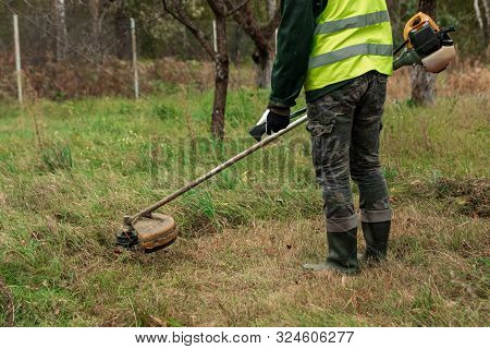 A Working Man In Professional Outfit Mows Grass With A Trimmer, A Mower. Mowing Lawns, Roadsides, Ed