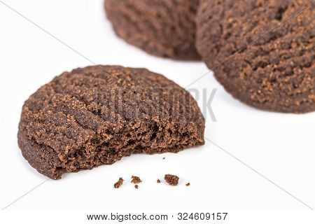 Dilicious Chocolate Rounded Cookies On White Plate With Bite Marks