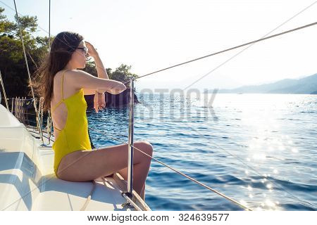 Attractive Young Woman In A Bright Yellow One-piece Swimsuit Sits On The Deck Of A Sailing Yacht. Se