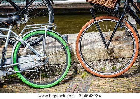 Bicycles With Blak, Green And Orange Tires On Brick Straat