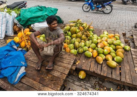Male, Maldives - November 16, 2017: Vendor Sells Coconuts On The Street In Cloudy Weather In Male, C