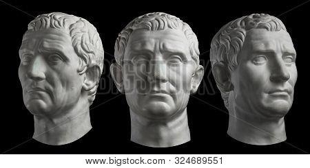 Three Gypsum Copy Of Ancient Statue Head Of Guy Julius Caesar Isolated On Black Background. Plaster