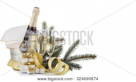 Still life with cooled champagne bottle  standing  in a bucket with ice, two full champagne flutes and Christmas ornaments  isolated on a white background with copy space, Christmas and New Year