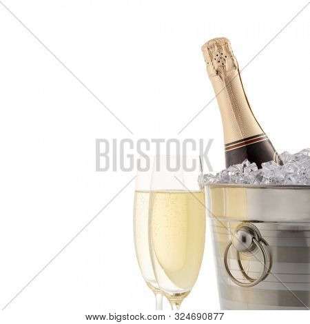 Still life with cooled champagne bottle standing in a bucket with ice and two full champagne flutes isolated on a white background