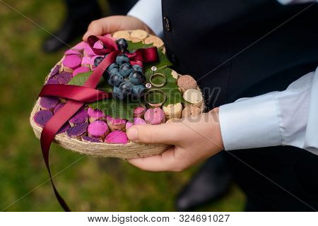 Golden Wedding Rings, Grapes And Champagne Corks Wedding Decor, Close-up. Rustic Wedding Ring Bearer