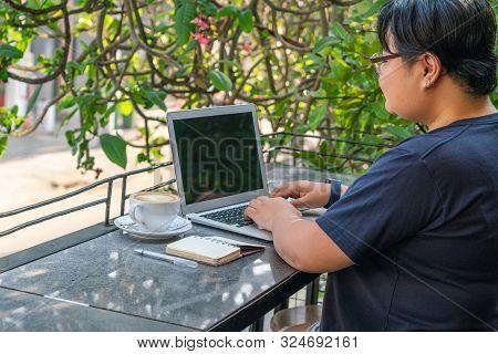 Asian Lesbian Freelance On Laptop At Beautiful Outdoor Coffeeshop