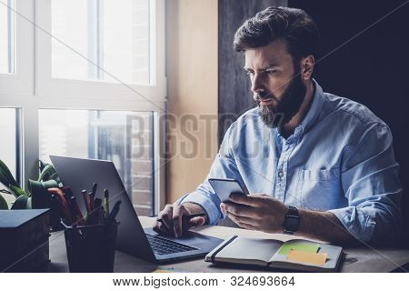 Young Man Sitting At Window, Working On Laptop. Bearded Man Wearing Smart Casual Clothes Sitting At