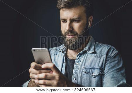 Bearded Man In Denim Jacket Using Smartphone In Everyday Life. Modern Lifestyle Of Digital Specialis