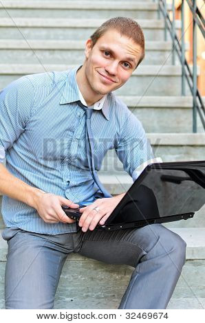 Young Guy With A Laptop Sitting On The Stairs